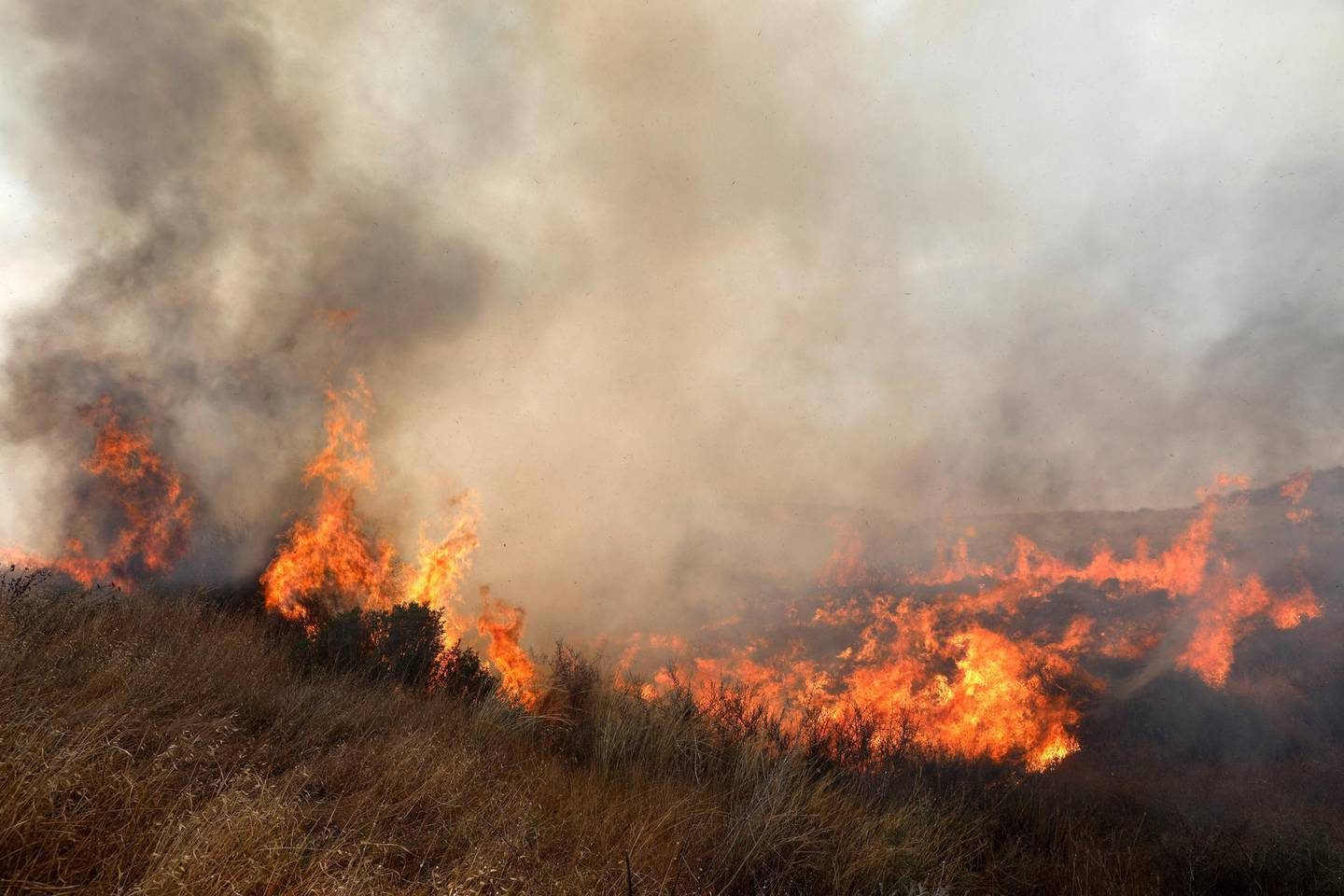 epa06786264 Fire that ignited at a field as a result of a Molotov cocktail kite that was sent from Gaza Strip few kilometers from the border with Gaza near Kibbutz Or Haner, in southern Israel, 05 June 2018. Media reports that after a cease-fire was achieved betweeen Israeli military and Palestinian militants in Gaza on 29 May 2018 Palestinians from Gaza continue to send Molotov kites to the Israeli territory and cause damage to thousands of acres of agriculture and nature reserves in Israel as Palestinians mark the 'Naksa Day' or the so-called Six-days war.  EPA/ABIR SULTAN