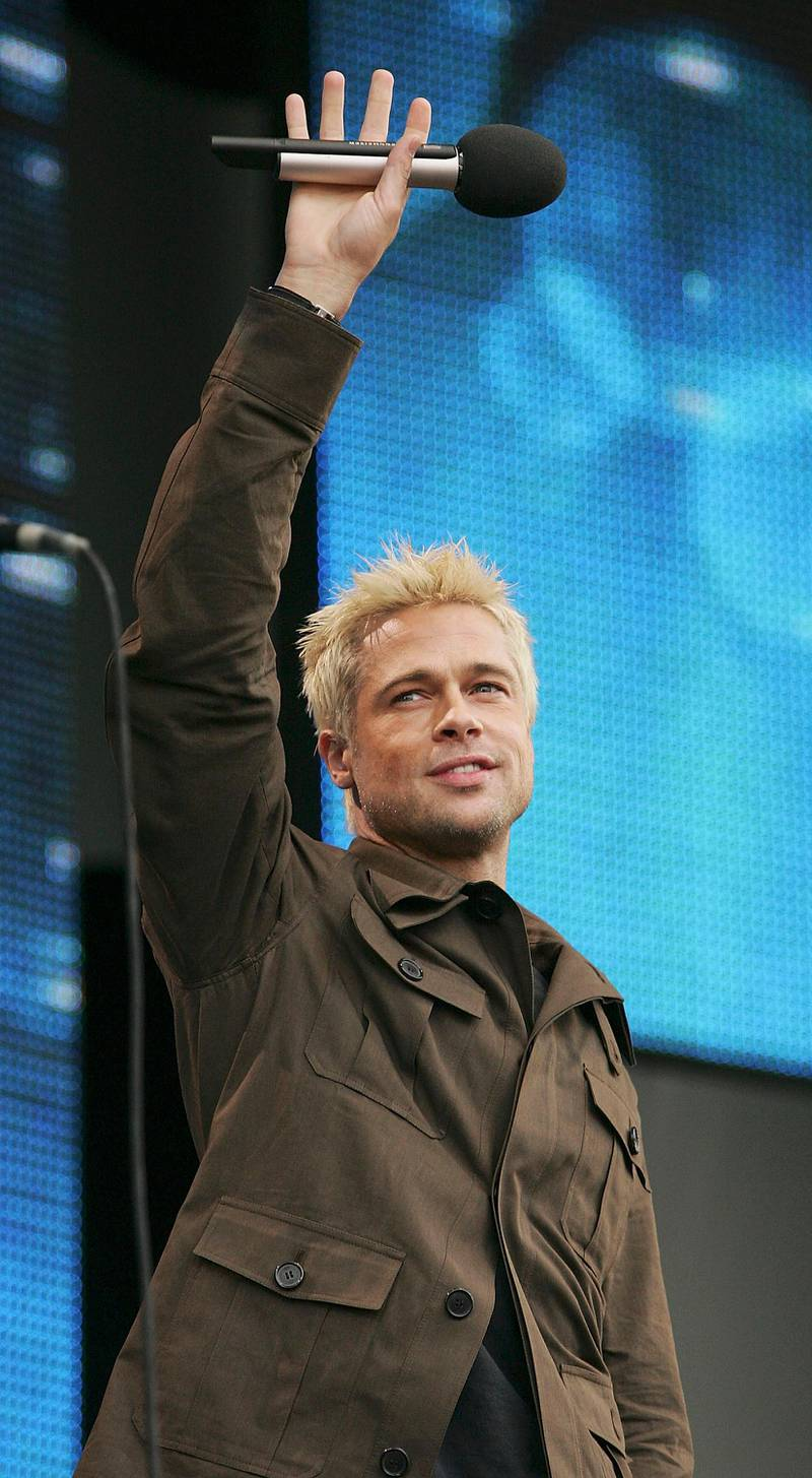 """LONDON - JULY 02:  Actor Brad Pitt on stage at """"Live 8 London"""" in Hyde Park on July 2, 2005 in London, England.  The free concert is one of ten simultaneous international gigs including Philadelphia, Berlin, Rome, Paris, Barrie, Tokyo, Cornwall, Moscow and Johannesburg.  The concerts precede the G8 summit (July 6-8) to raising awareness for MAKEpovertyHISTORY.  (Photo by MJ Kim/Getty Images)"""