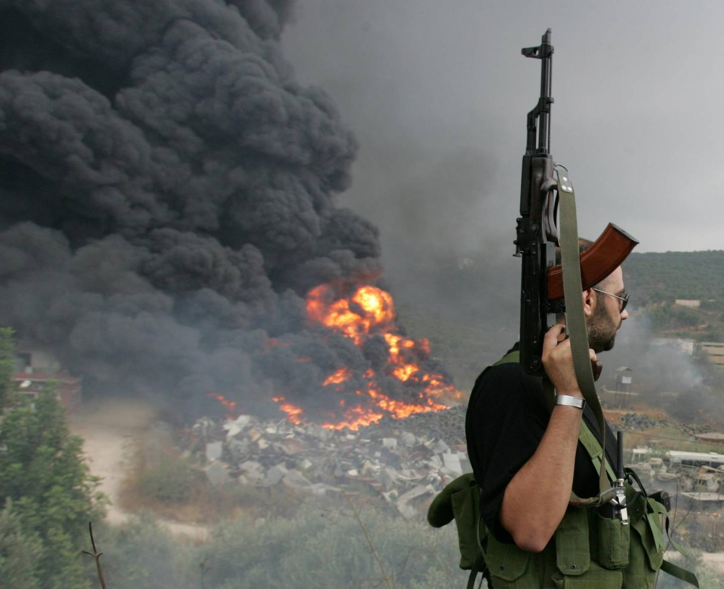 FILE PHOTO: A Lebanese Hezbollah guerrilla looks at a fire rising from a burning object in a Beirut suburb, Lebanon July 17, 2006. REUTERS/Issam Kobeisi/File Photo