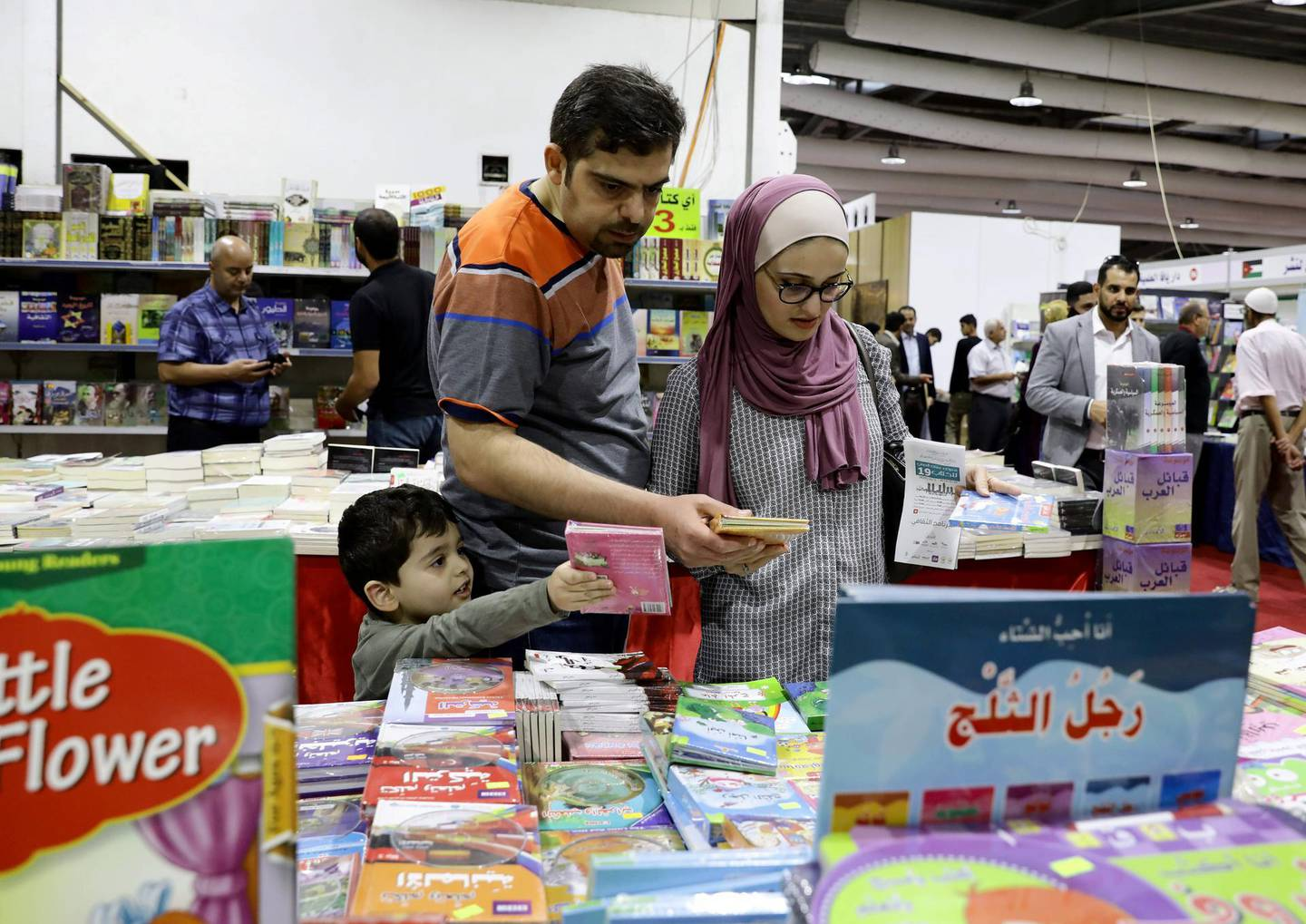 epa07871847 Visitors look at children's books presented at the 19th Amman  International Book Fair, in Amman, Jordan, 26 September 2019. The event opened its doors on 26 September and is due to last until 05 October, featuring publishers from the Arab world with their own books in Arabic and English as well as non-Arabic publications they import. The 19th edition's guest of honor is Tunisia.  EPA-EFE/AMEL PAIN *** Local Caption *** 55498029