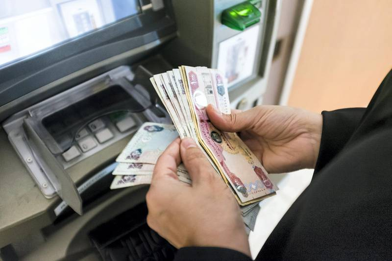 DUBAI, UNITED ARAB EMIRATES - Jan 24, 2018. A woman withdraws cash from Dubai Islamic Bank's ATM in Dubai Mall.(Photo by Reem Mohammed/The National)Reporter:  Section: NA