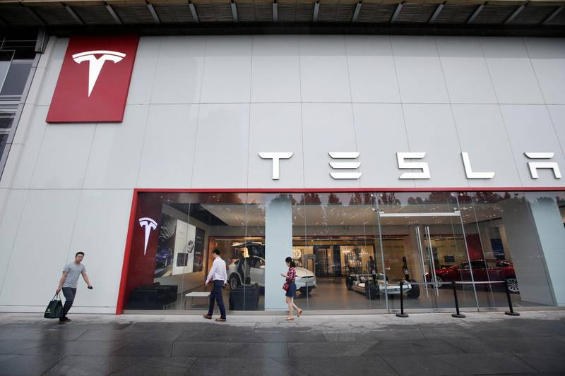 People walk past a showroom outside Tesla China headquarters at China Central Mall in Beijing, China July 11, 2018. REUTERS/Jason Lee