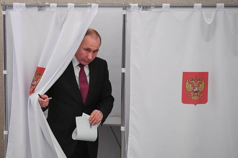 Presidential candidate, President Vladimir Putin walks out of a voting booth at a polling station during Russia's presidential election in Moscow on March 18, 2018. (Photo by Yuri KADOBNOV / POOL / AFP)