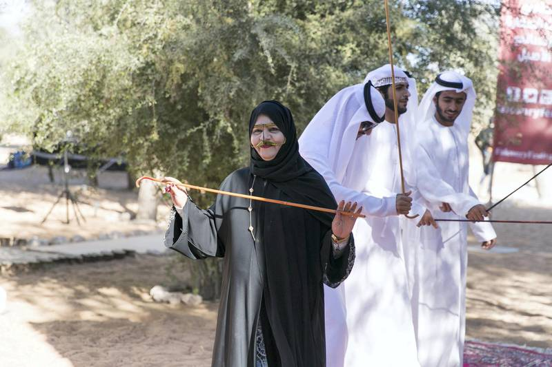 ABU DHABI, UNITED ARAB EMIRATES - DEC 6, 2017  A woman joins in the ayalla performers at the fourth International Festival of Falconry.   This gathering is a tribute to a similar meeting 41 years ago, in 1976, when the UAE Founding Father Sheikh Zayed invited falconers from around the world to convene in the desert of Abu Dhabi and build a strategy for the sport's development.  (Photo by Reem Mohammed/The National)  Reporter: Anna Zacharias Section: NA
