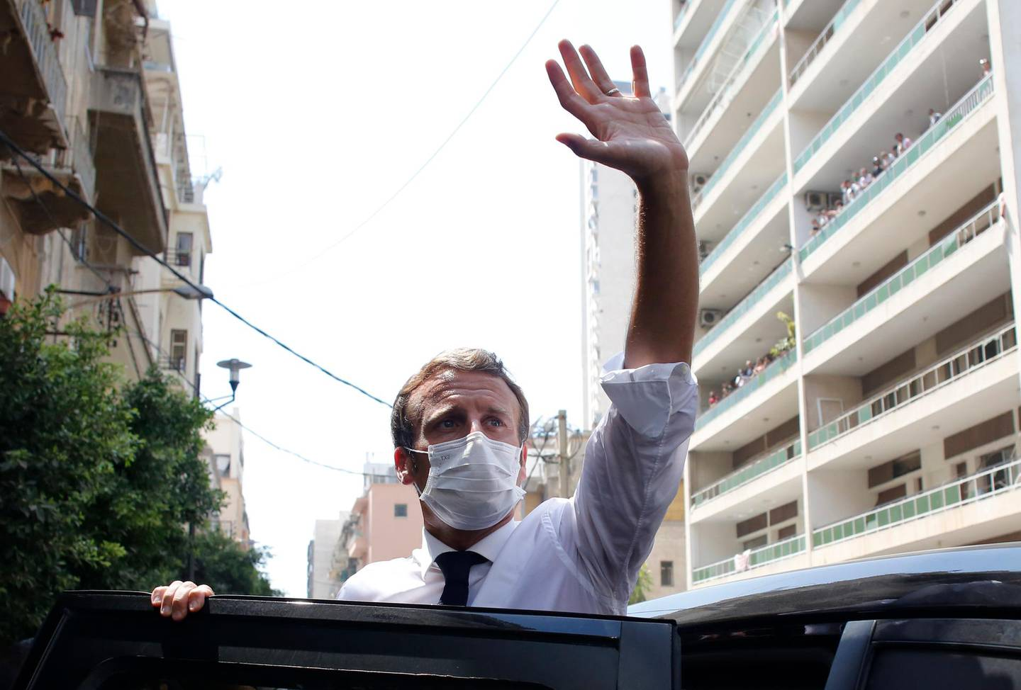 FILE - In this file photo dated Thursday Aug.6, 2020, French President Emmanuel Macron waves as he visits Beirut, Lebanon.  Frenchman Alain Cocq who suffers from a long-term and incurable degenerative illness had planned to show what he expects will be a painful end to his life, but Facebook said Saturday Sept. 5, 2020, it has blocked his live broadcasts and President Macron has said that French law forbade him for granting Cocq's request for a medically-assisted death. (AP Photo/Thibault Camus, FILE)