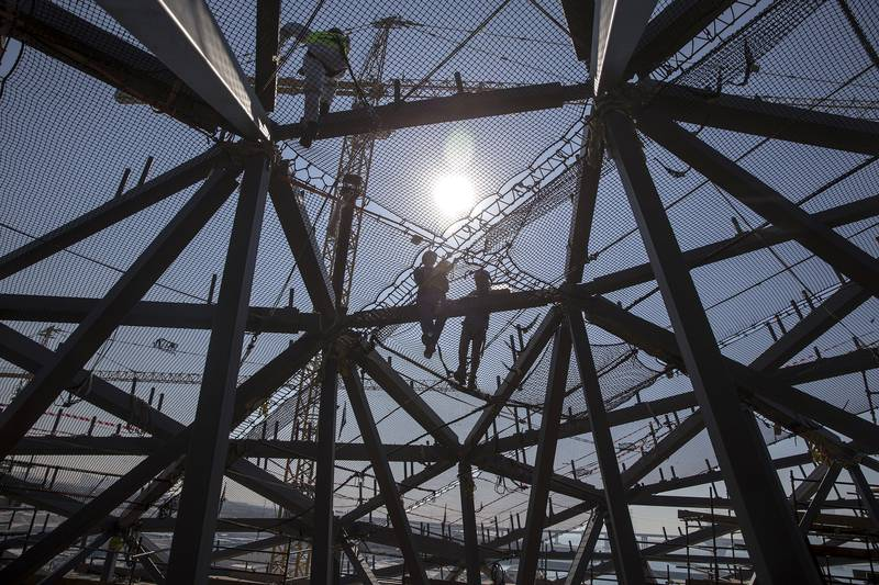 ABU DHABI, UNITED ARAB EMIRATES, Jan. 24, 2015:   Seen through super-sized elements are men working, harnessed-in above safety nets and hanging scaffolds, which will be used as platforms to install the dome's outer cladding the Louvre Abu Dhabi dome on Saturday, Jan. 24, 2015, at the gallery's construction site on Saadiyat Island in Abu Dhabi.  (Silvia Razgova / The National)  /  Usage: RESTRICTED /  Section: NA  /  Reporter:  Nick Leech *** Local Caption ***  SR-150124-LAD0312.jpg SR-150124-LAD0312.jpg