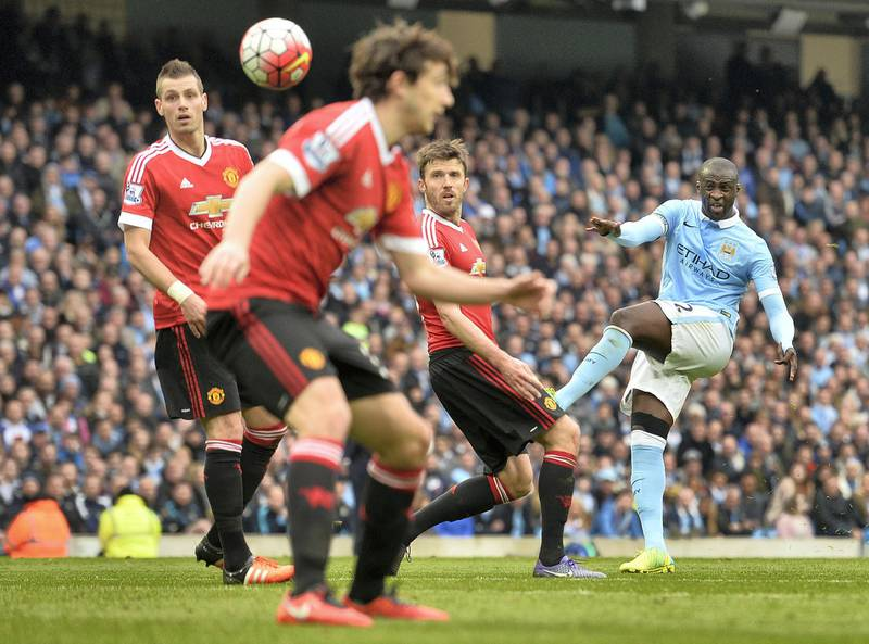 Manchester City's Ivorian midfielder and captain Yaya Toure (R) attempts a shot on goal during the English Premier League football match between Manchester City and Manchester United at the Etihad Stadium in Manchester, north west England, on March 20, 2016. (Photo by PAUL ELLIS / AFP) / RESTRICTED TO EDITORIAL USE. No use with unauthorized audio, video, data, fixture lists, club/league logos or 'live' services. Online in-match use limited to 75 images, no video emulation. No use in betting, games or single club/league/player publications. /