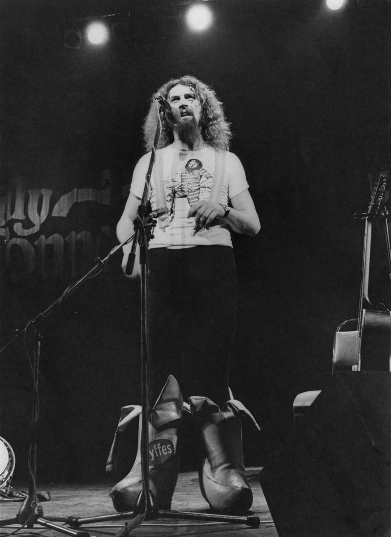 Scottish comedian Billy Connolly performing on stage in a pair of outsize, banana-shaped boots, 7th July 1977.  (Photo by Evening Standard/Hulton Archive/Getty Images)