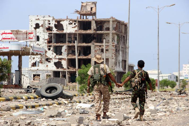 epa07934862 Members of Houthi militia pass a destroyed building during the deployment of observers on cross-lines in Hodeidah, Yemen, 19 October 2019. According to reports, Lieutenant General of India Abhijit Guha, chair of the UN's redeployment coordination committee in the Yemeni city of Hodeidah, oversaw the deployment of observers on cross-lines and checkpoints in Hodeidah to stabilize the ceasefire and activate a new procedure for de-escalation in the port city between the Houthi rebels and the Saudi-backed government forcers. Hodeidah is the key lifeline entry point for most of the Arab country's food imports and humanitarian aid.  EPA/NAJEEB ALMAHBOOBI