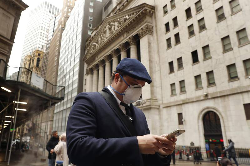 FILE PHOTO: A man wears a protective mask as he walks past the New York Stock Exchange on the corner of Wall and Broad streets during the coronavirus outbreak in New York City, New York, U.S., March 13, 2020. REUTERS/Lucas Jackson/File Photo