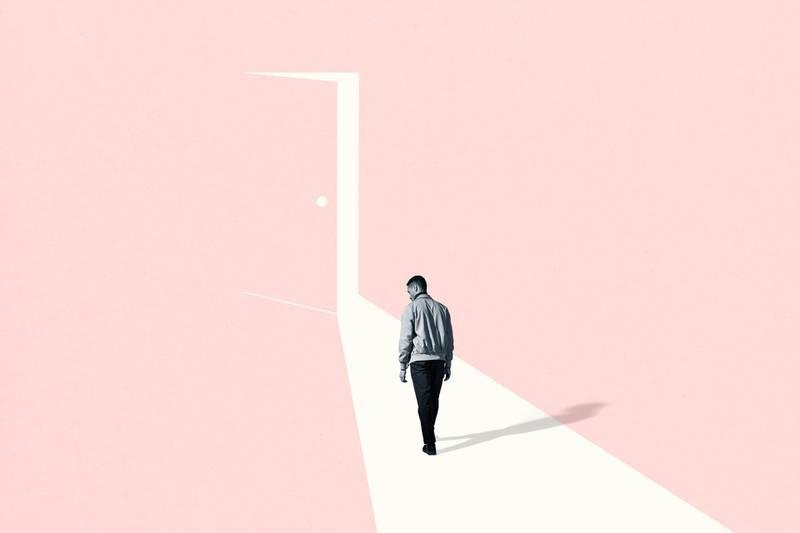 Full length rear view of sad young man walking towards ajar door. Getty Images