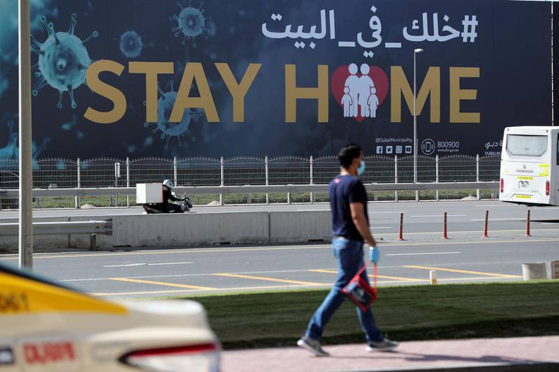 Dubai, United Arab Emirates - Reporter: N/A: Coronavirus/Covid-19. A man walks passed a huge sign on Sheikh Zayed Road that says 'Stay Home'. Tuesday, May 5th, 2020. Dubai. Chris Whiteoak / The National