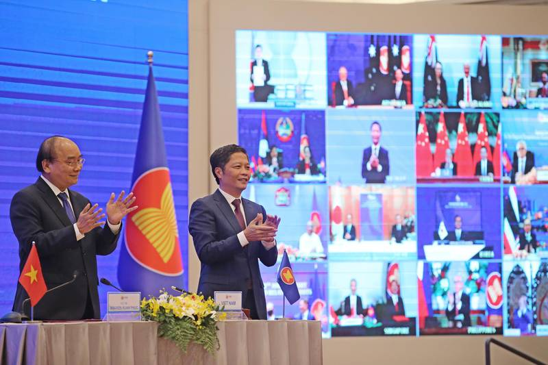 epa08821142 Vietnam's Prime Minister Nguyen Xuan Phuc (L) and Minister of Industry and Trade Tran Tuan Anh (R) cheer during the virtual signing ceremony for the Regional Comprehensive Economic Partnership (RCEP) in Hanoi, Vietnam, 15 November 2020. The virtual 37th ASEAN Summit and related summits take place from 12 to 15 November 2020 at the International Convention Center (ICC) in Hanoi.  EPA/LUONG THAI LINH