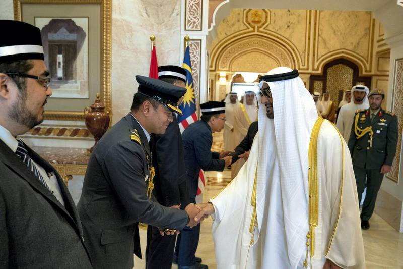 ABU DHABI, UNITED ARAB EMIRATES - June 14, 2019: HH Sheikh Mohamed bin Zayed Al Nahyan, Crown Prince of Abu Dhabi and Deputy Supreme Commander of the UAE Armed Forces (R) bids farewell to members of the delegation accompanying HM King Sultan Abdullah Sultan Ahmad Shah of Malaysia (not shown), at the Presidential Airport.  ( Hamad Al Kaabi / Ministry of Presidential Affairs ) ---
