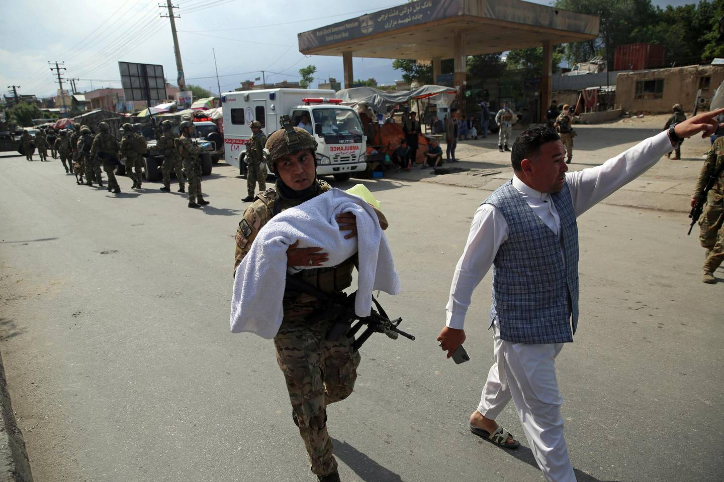 An Afghan security officer carries a baby after gunmen attacked a maternity hospital, in Kabul, Afghanistan, Tuesday, May 12, 2020. Gunmen stormed the hospital in the western part of Kabul on Tuesday, setting off a shootout with the police and killing several people. (AP Photo/Rahmat Gul)