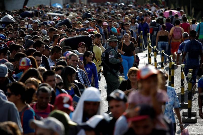 FILE PHOTO: A Venezuelan National Guard stands next to people queueing to try to cross into Colombia from Venezuela through Simon Bolivar international bridge in San Antonio del Tachira, Venezuela January 24, 2018. REUTERS/Carlos Garcia Rawlins/File Photo