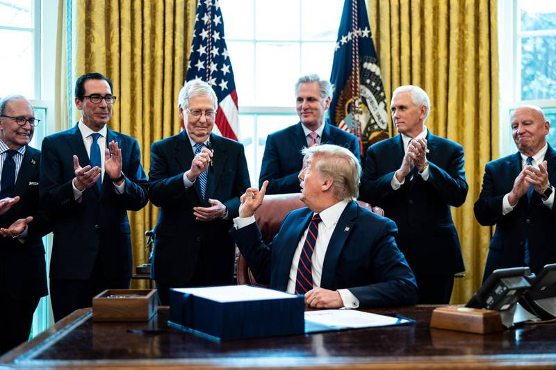 epaselect epa08327641 US President Donald J. Trump (C) hands a pen to Republican Senate Majority Leader Mitch McConnell (3-L) during a signing ceremony for the The CARES Act in the Oval Office at the White House in Washington, DC, USA on 27 March 2020. The CARES Act, is a coronavirus COVID-19 stimulus package worth more than two trillion US dollars.  EPA/Erin Schaff / POOL