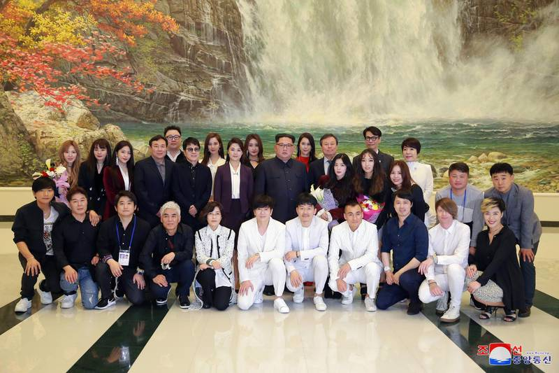 epa06641310 A picture made released by the North Korean Central News Agency (KCNA), the state news agency of North Korea, shows Respected Supreme Leader Kim Jong-un (C), together with his wife Ri Sol Ju, posing for a group photograph with artists after enjoying the performance 'Spring Comes', given by an art troupe from South Korea, at the East Pyongyang Grand Theatre in Pyongyang, North Korea, 01 April 2018 (issued 02 April 2018).  EPA/KCNA