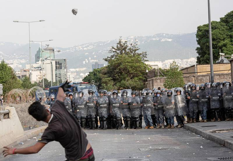 BEIRUT, LEBANON - OCTOBER 30: A demonstrator throws stones at police at an anti-France protest on October 30, 2020 in Beirut, Lebanon. Following a series of deadly attacks, France's President Macron declared a crackdown on Islamist extremism by shutting down mosques and other organisations accused of instigating violence. The comments sparked protests across the Muslim world and calls for a boycott of French goods. (Photo by Sam Tarling/Getty Images)