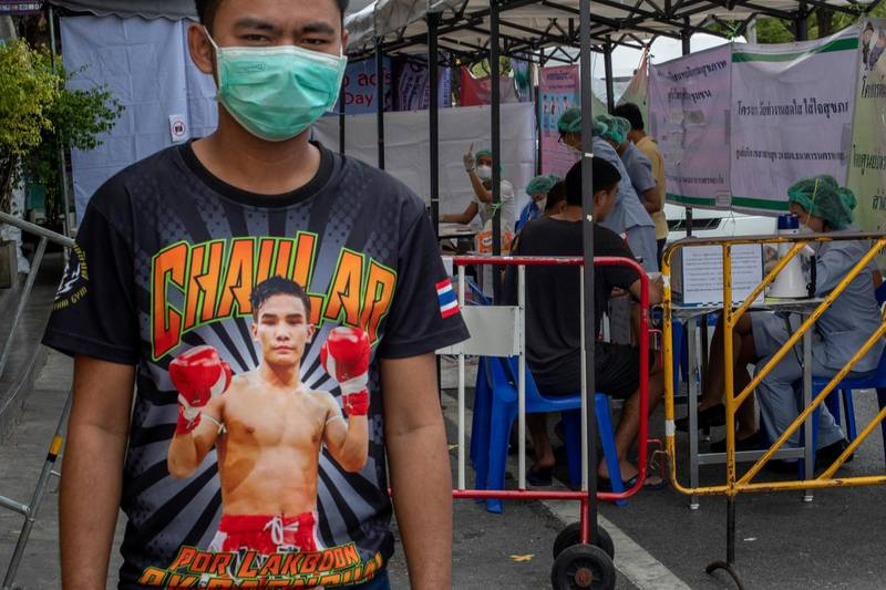 In this Thursday, March 19, 2020, photo, a Muay Thai boxing fighter stands in front of makeshift screening facility outside Rajadamnern boxing stadium in Bangkok, Thailand. Kickboxing aficionados came from all over Thailand to attend a major Muay Thai tournament at Bangkok's indoor Lumpini Stadium on March 6, 2020. Dozens or more went home unknowingly carrying the coronavirus. For most people the new COVID-19 coronavirus causes only mild or moderate symptoms, but for some it can cause more severe illness. (AP Photo/Gemunu Amarasinghe)