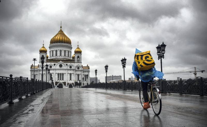 A food delivery courier rides in front of Christ-the-Savior cathedral in central, the main Russian Orthodox church in central Moscow, on June 2, 2020, amid the outbreak of COVID-19, caused by the novel coronavirus, as Moscow authorities started opening churches, mosques and synagogues. (Photo by Alexander NEMENOV / AFP)