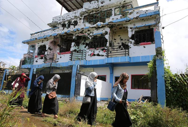 Residents who returned from evacuation centers walk past a bullet-ridden house believed to have been rented by pro-Islamic State militant group leaders Isnilon Hapilon and Omar Maute before their attack on the region, in Basak, Malutlut district in Marawi city, Philippines October 29, 2017. REUTERS/Romeo Ranoco