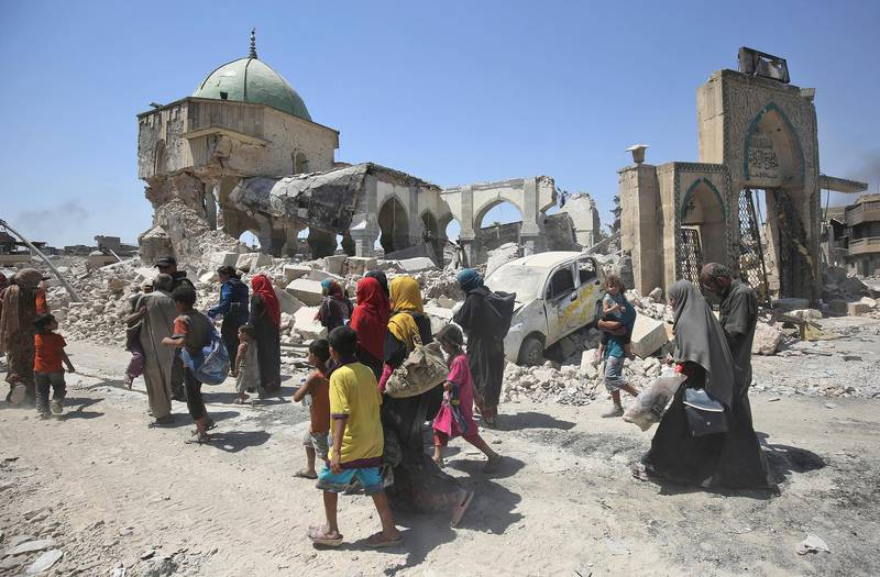 Iraqis walk by the destroyed Al-Nuri Mosque as they flee from the Old City of Mosul on July 5, 2017, during the Iraqi government forces' offensive to retake the city from Islamic State (IS) group fighters. - Iraqi forces have been closing in on the Old City in west Mosul for months, but the terrain combined with a large civilian population has made for an extremely difficult fight. (Photo by AHMAD AL-RUBAYE / AFP)