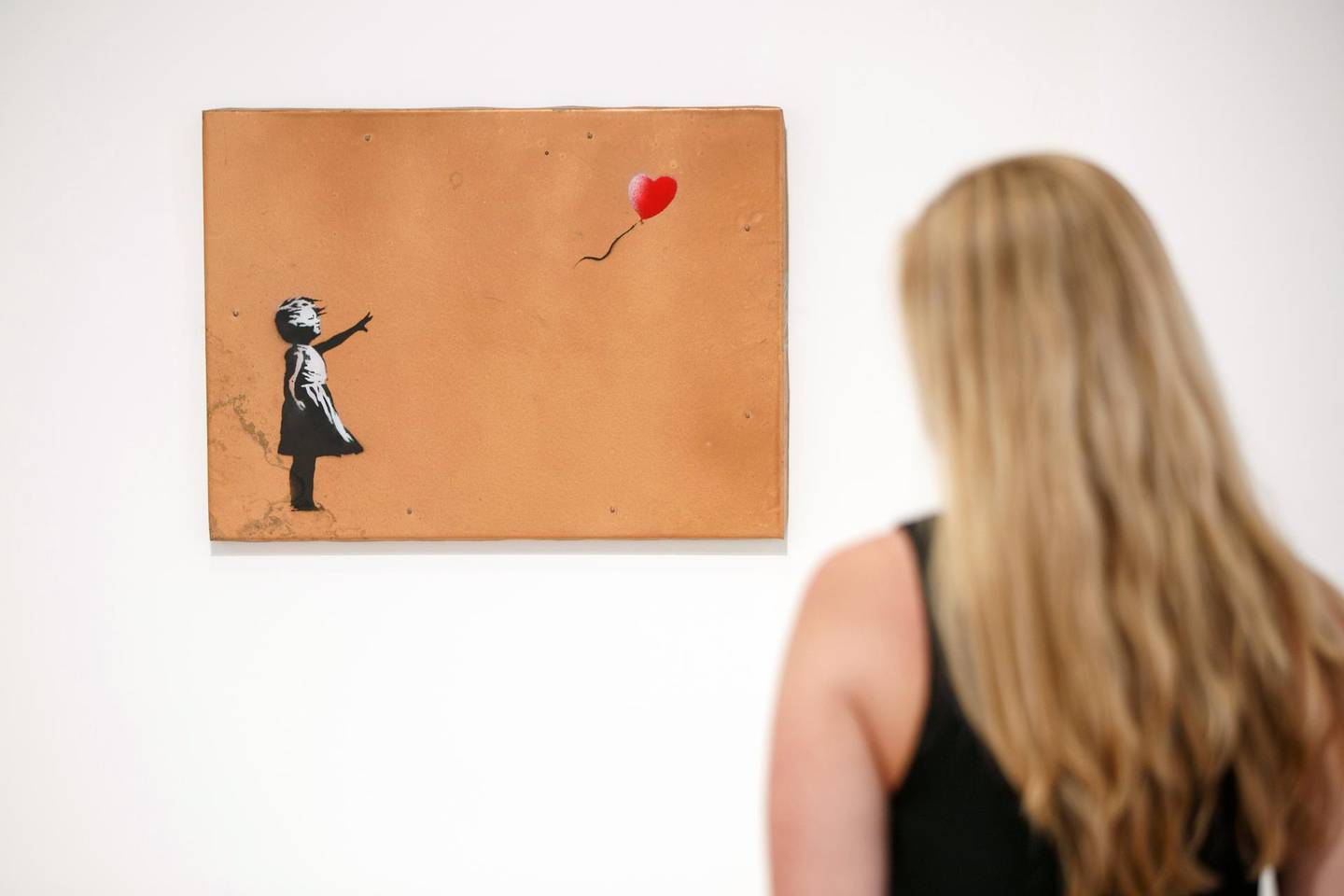 A gallery assistant poses with 'Girl with Balloon' 2006 artwork by Banksy at Lazinc Gallery in London on July 11, 2018. The exhibition opens to the public on July 12, 2018. / AFP PHOTO / Tolga AKMEN / RESTRICTED TO EDITORIAL USE - MANDATORY MENTION OF THE ARTIST UPON PUBLICATION - TO ILLUSTRATE THE EVENT AS SPECIFIED IN THE CAPTION