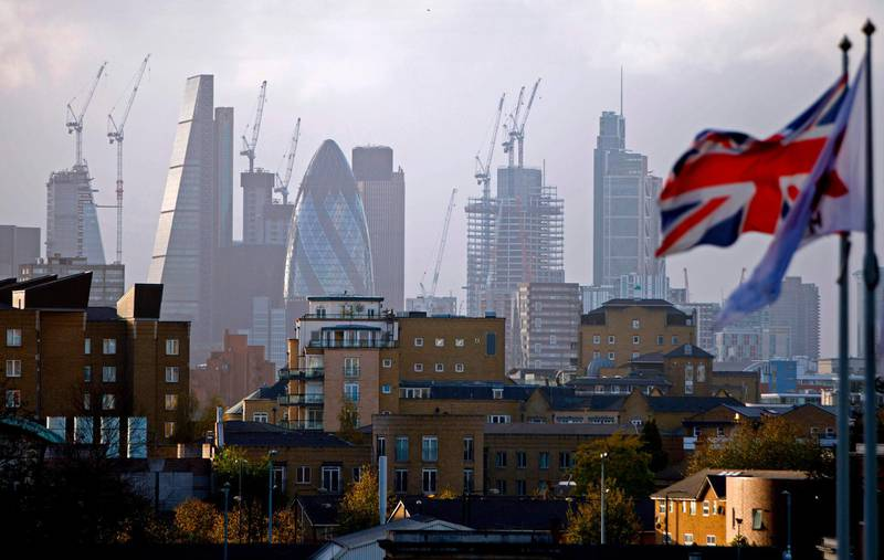 """(FILES) In this file photo taken on October 21, 2017 A Union flag flies from a pole as construction cranes stand near skyscrapers in the City of London, including the Heron Tower, Tower 42, 30 St Mary Axe commonly called the """"Gherkin"""", the Leadenhall Building, commonly called the """"Cheesegrater"""", as they are pictured beyond blocks of residential flats and apartment blocks, from east London on October 21, 2017. Britain will slide into a year-long recession should it leave the European Union without a deal with Brussels, the government's official forecaster said on July 18, 2019. / AFP / Tolga AKMEN"""