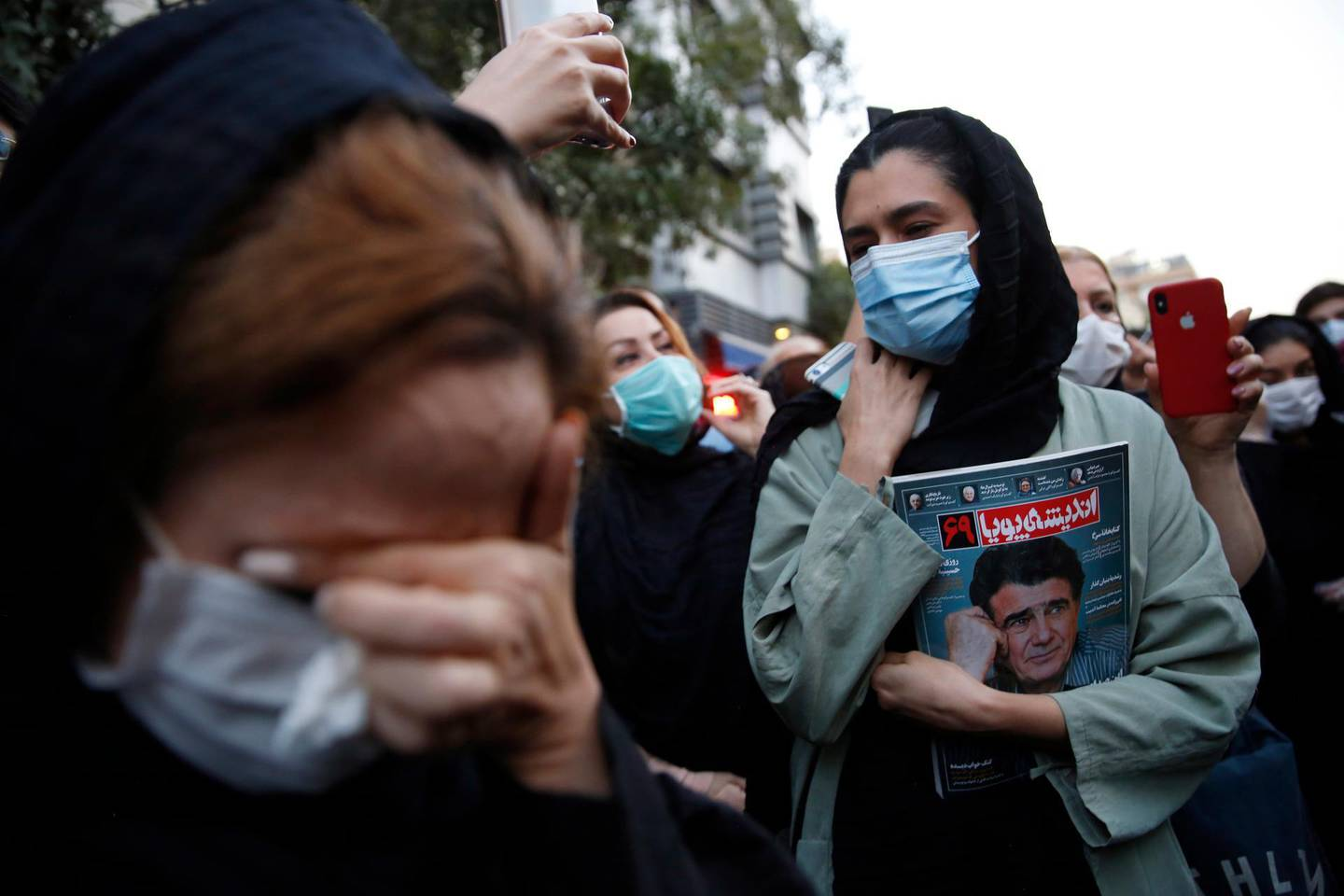 epa08729608 Female fans of Iran's legendary singer, instrumentalist, and composer Mohammad-Reza Shajarian, with one holding a picture of him, mourn in front of the Jam hospital, where Shajarian reportedly passed away, in Tehran, Iran, 08 October 2020. Shajarian, who embodied traditional and classical music in Iran, died in Tehran after a long battle with an illness.  EPA/ABEDIN TAHERKENAREH