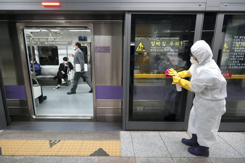 A worker wearing protective gears disinfects a door as a precaution against the new coronavirus at a subway station in Seoul, South Korea, Friday, Feb. 28, 2020. Japan's schools prepared to close for almost a month and entertainers, topped by K-pop superstars BTS, canceled events as a virus epidemic extended its spread through Asia into Europe and on Friday, into sub-Saharan Africa. (AP Photo/Ahn Young-joon)