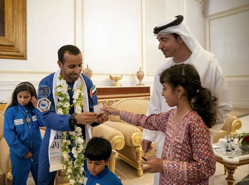 ABU DHABI, UNITED ARAB EMIRATES - October 12, 2019: Hazza Ali Al Mansoori, the first UAE Astronaut to be deployed on a space mission to the International Space Station (ISS) (3rd R), receives a note from HH Sheikha Fatima bint Mohamed bin Hamad bin Tahnoon Al Nahyan (R). Seen with HH Sheikh Hazza bin Zayed Al Nahyan, Vice Chairman of the Abu Dhabi Executive Council (2nd R).  ( Hamad Al Kaabi / Ministry of Presidential Affairs ) ---