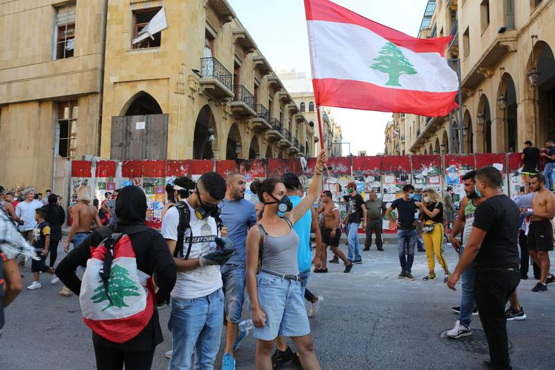 epa08595570 Protesters wave a Lebanese flag during protests near the parliament in Beirut, Lebanon, 10 August 2020. According to reports, anti-government protests continued in Lebanon despite the resignation of three ministers and several members of the parliament, as protesters are demanding the resignation of the government and all those responsible for the port explosion be held accountable. Beirut governor said at least 200 people were killed in the explosion on 04 August and dozens are still missing.  EPA/NABIL MOUNZER