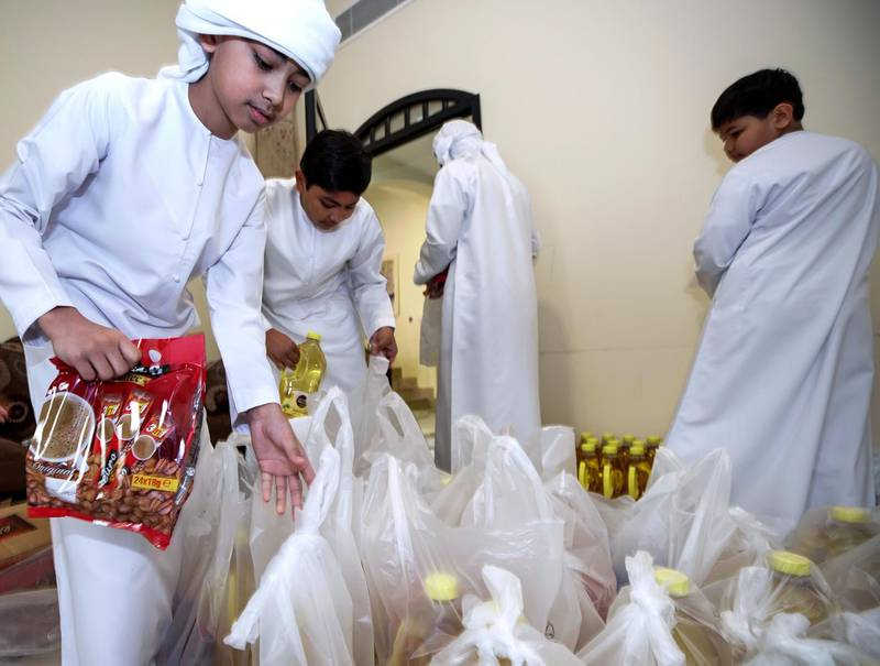Abu Dhabi, United Arab Emirates, April 30, 2020.    Filipino woman, Mona Mohamed Baraguir who donates rice, eggs, cooking oil and other daily essentials to laid off workers.Mona with her children, (L-R) Fares-9, Hamed Khalifa-15,  Ali-13 and Saed- 11. The boys help pack the daily supplies.Victor Besa / The NationalSection:  NAReporter:  Shireena Al Nuwais