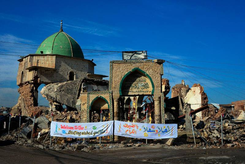 """TOPSHOT - A picture taken on December 16, 2018, shows the Great Mosque of al-Nuri and the remains of """"Al-Hadba"""" leaning minaret in Mosul's war-ravaged Old City, during the placing of the corner stone ceremony. The famed 12th century mosque and minaret, dubbed Al-Hadba or """"the hunchback,"""" were where IS chief Abu Bakr al-Baghdadi made his only public appearance to declare a self-styled """"caliphate"""" after sweeping into Mosul in 2014. The structures were ravaged three years later in the final, most brutal stages of the months-long fight against IS.  / AFP / Zaid AL-OBEIDI"""