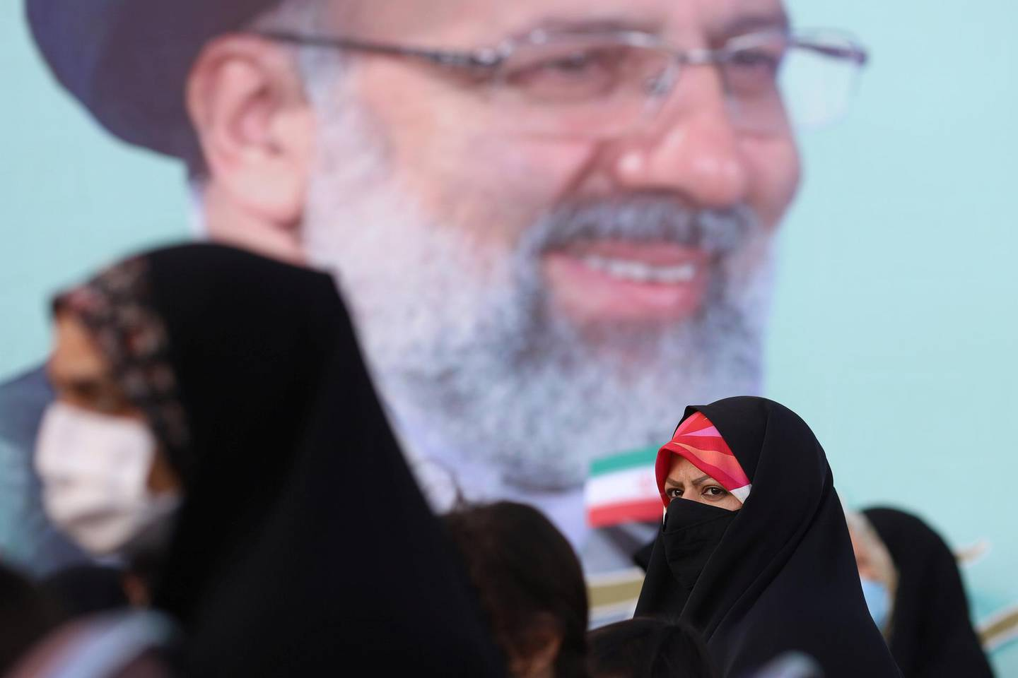 Supporters of Ebrahim Raisi gather near his poster to celebrate his presidential election victory in Tehran, Iran June 19, 2021. Majid Asgaripour/WANA (West Asia News Agency) via REUTERS ATTENTION EDITORS - THIS IMAGE HAS BEEN SUPPLIED BY A THIRD PARTY.