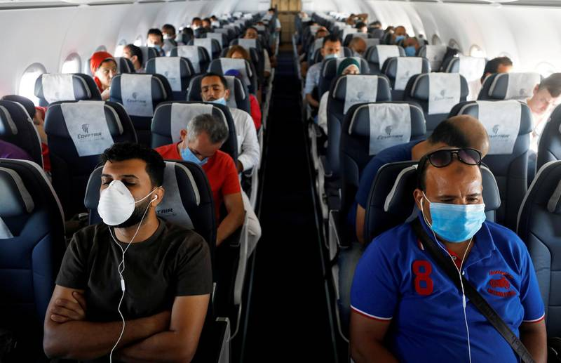 FILE PHOTO: Passengers wearing protective face masks sit on a plane at Sharm el-Sheikh International Airport, following the outbreak of the coronavirus disease (COVID-19), in Sharm el-Sheikh, Egypt, June 20, 2020. REUTERS/Mohamed Abd El Ghany/File Photo/File Photo