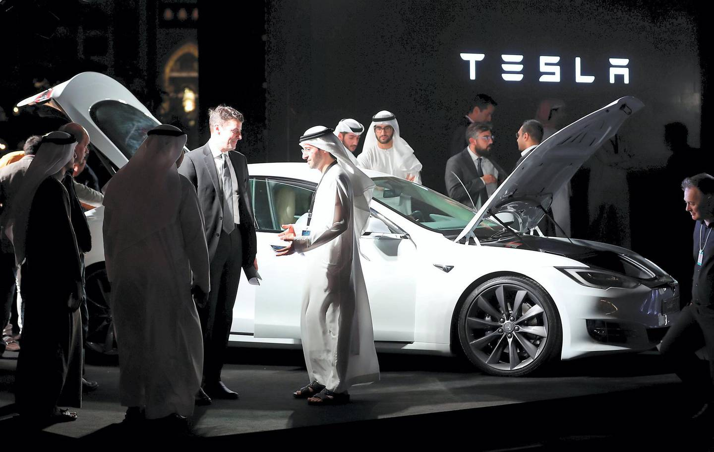 Emirati men check a vehicle manufactured by Electric carmaker Tesla during a ceremony in Dubai, on February 13, 2017.   Tesla announced the opening of a new Gulf headquarters in Dubai, aiming to conquer an oil-rich region better known for gas guzzlers than environmentally friendly motoring. / AFP PHOTO / KARIM SAHIB