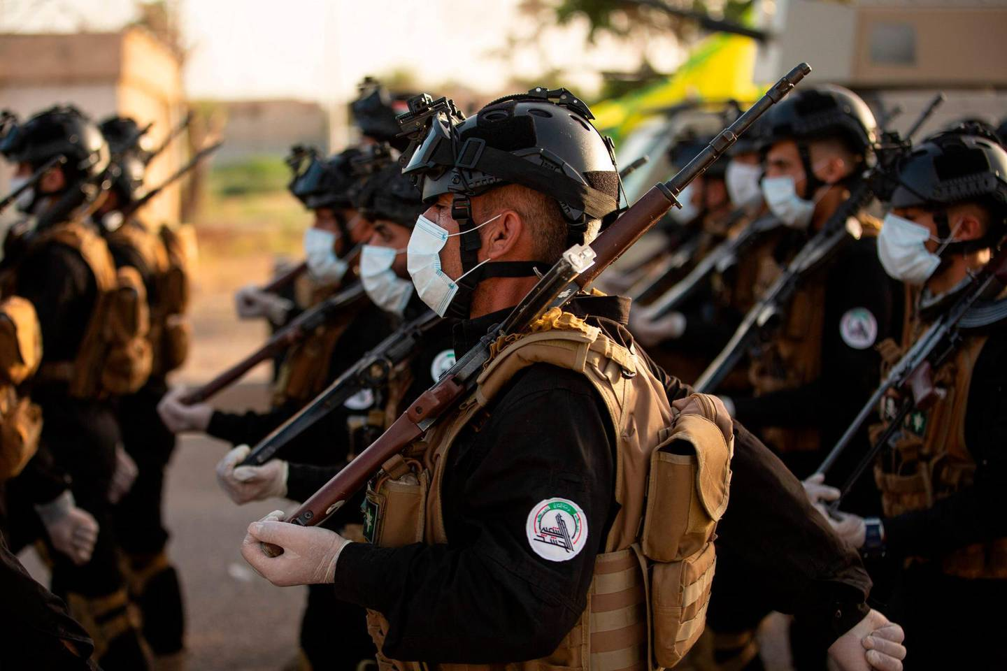 (FILES) In this file photo taken on June 14, 2020 Mask-clad members of the Hashed al-Shaabi (Popular Mobilisation) paramilitary force take part in a military parade in the southern Iraqi city of Basra, marking the sixth anniversary of its founding after Iraq's top Shiite cleric Grand Ayatollah Ali Sistani called to defend the country from the Islamic State group (IS). Around the corner from Iraq's holiest shrines, a years-long struggle over resources and reputations is coming to a head -- threatening a dangerous schism within a powerful state-sponsored security force. The growing fissure pits the vast Iran-aligned wing of the Hashed al-Shaabi network against four factions linked to the shrines of Iraq's twin holy cities, Karbala and Najaf. / AFP / Hussein FALEH