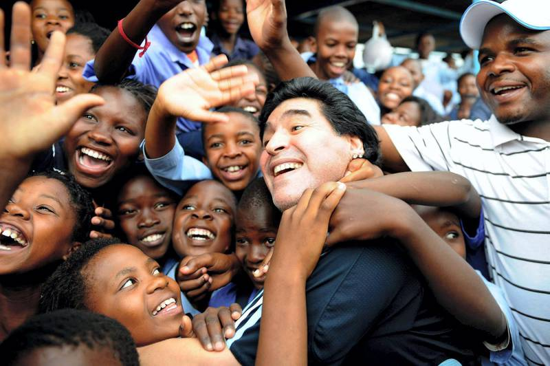 WINTERVELDT, SOUTH AFRICA - JANUARY 19:  In this handout photo provided by 2010 FIFA World Cup Organising Committee South Africa, Argentina national soccer team's head coach Diego Maradona is greeted by schoolchildren during his visit to Kgotlelelang School at Winterveldt on January 19, 2010, around 40km north west of Pretoria, South Africa.  (Photo by 2010 FIFA World Cup Organising Committee South Africa via Getty Images)