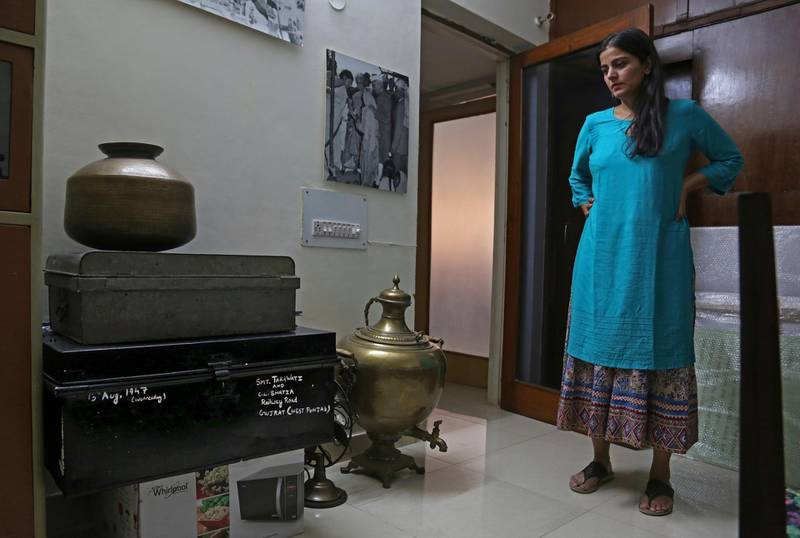 In this July 22, 2017 photograph, CEO of India's new partition museum Mallika Ahluwalia looks at a steel trunk, black, which was among items donated by the relative of a person who had migrated to India during partition in 1947, in New Delhi, India. A new museum on the Partition of the Indian subcontinent opens this week, in the north Indian border city of Amritsar, as the two South Asian giants celebrate seven decades as independent nations. (AP Photo/Altaf Qadri)