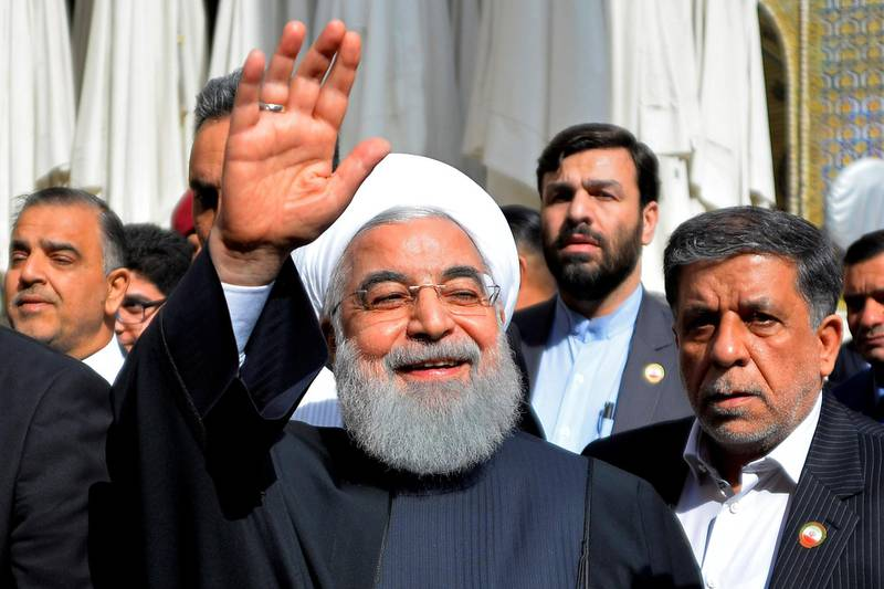 """Iranian President Hassan Rouhani (C) visits in the Iraqi central city of Najaf on March 13, 2019. - Iran's President Hassan Rouhani hit back on March 11 against pressure from the """"aggressor"""" United States on Iraq to limit ties with its neighbour, during his first official visit to Baghdad. Shiite-majority Iraq is walking a fine line to maintain good relations with its key partners Iran and the United States which themselves are arch-foes. (Photo by Haidar HAMDANI / AFP)"""