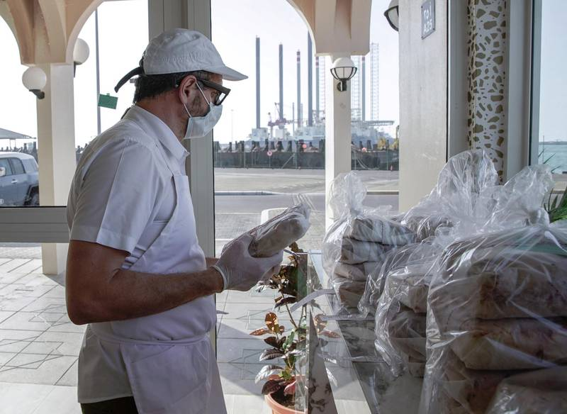 Abu Dhabi, United Arab Emirates, May 14, 2020.    Raj Dagstani arranges his pre ordered pizzas ready for pick up in a Covid-19 compliant environment.Victor Besa / The NationalSection:  IFReporter:  Ann Marie McQueen