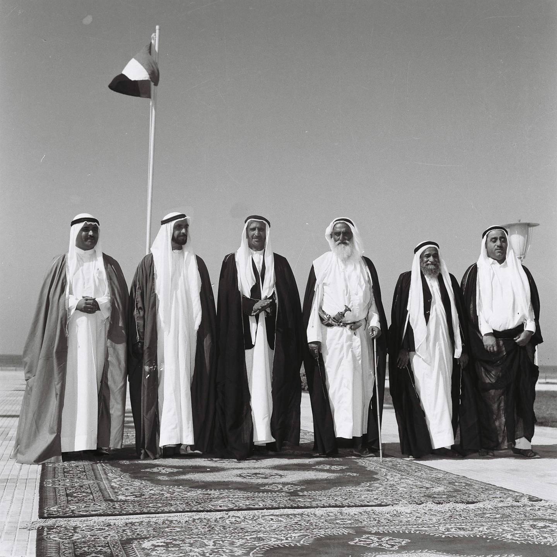 "History Project 2010, ""The First Day"". Sheikh Zayed and UAE rulers at Union House in Dubai. December 2, 1971. Sheikhs pictured from left-right :Sharjah - Sheikh Khalid Al Qasami, Abu Dhabi - Sheikh Zayed Al Nayhan (born 1981), Dubai - Sheikh Rashid Al Maktoum (born 1912) , Ajman - Sheikh Rashed Al Nuami (born 1902) Fujeirah - Sheikh Mohammed Al Sharqi, UAQ - Sheikh Ahmed Al' Mu'alla."
