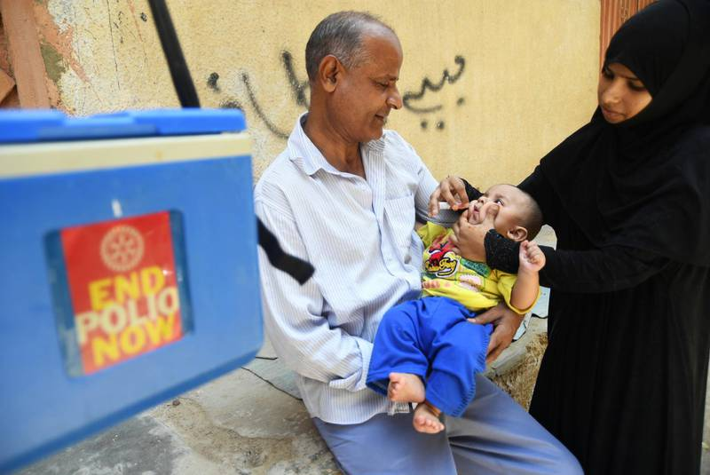 A Pakistani health worker administers polio vaccine drops to a child during a polio vaccination campaign in Karachi on May 7, 2018. - Pakistan is one of only two countries in the world where polio remains endemic. (Photo by ASIF HASSAN / AFP)