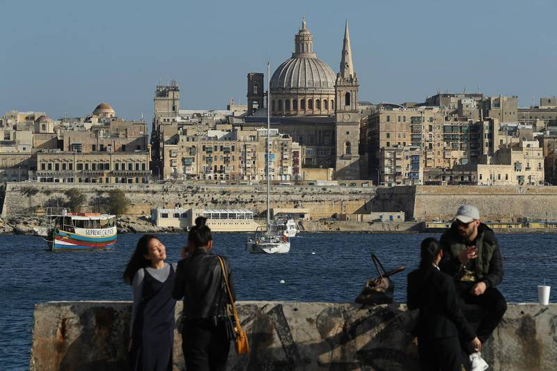 SLIEMA, MALTA - MARCH 29:  Young people relax and photograph each other as Valletta, including the dome of the Basilica of Our Lady of Mount Carmel, stands behind on March 29, 2017 in Sliema, Malta. Valletta, a fortfied town that dates back to the 16th century, is the capital of Malta and a UNESCO World Heritage Site. In the last 2,000 years Malta has been under Roman, Muslim, Norman, Knights of Malta, French and British rule before it became independent in 1964. Today Malta remains a crossroads of cultures and is a popular tourist destination.  (Photo by Sean Gallup/Getty Images)