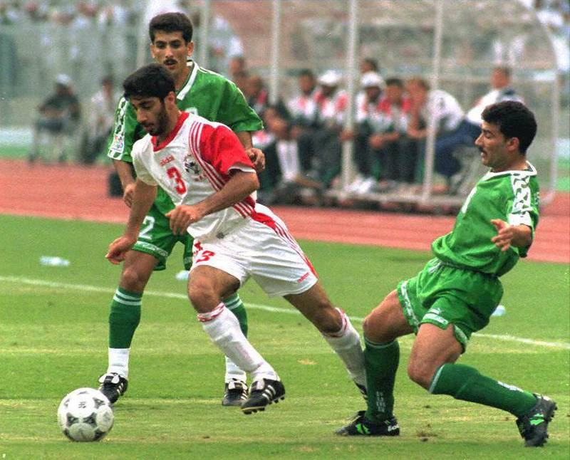 UAE's Munther Abdulla (C) dribbles past Iraqi defenders Hayder Majeed (L) and Esam Salem 15 December during their Asian Cup quarterfinal match in Abu Dhabi. (Photo by JORGE FERRARI / AFP)
