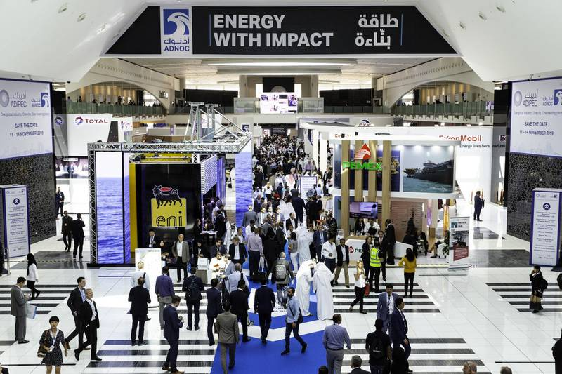 Delegates pass exhibitor's stands at the Abu Dhabi International Petroleum Exhibition & Conference (ADIPEC) in Abu Dhabi, United Arab Emirates, on Tuesday, Nov. 13, 2018. OPEC's secretary-general, energy ministers from Saudi Arabia to Russia, CEOs at oil majors from Total SA, BP Plc and Eni SpA, and officials from Middle Eastern energy giants such as Abu Dhabi's Adnoc have gathered to sign deals and discuss oil, gas, refining and petrochemical issues. Photographer: Christopher Pike/Bloomberg