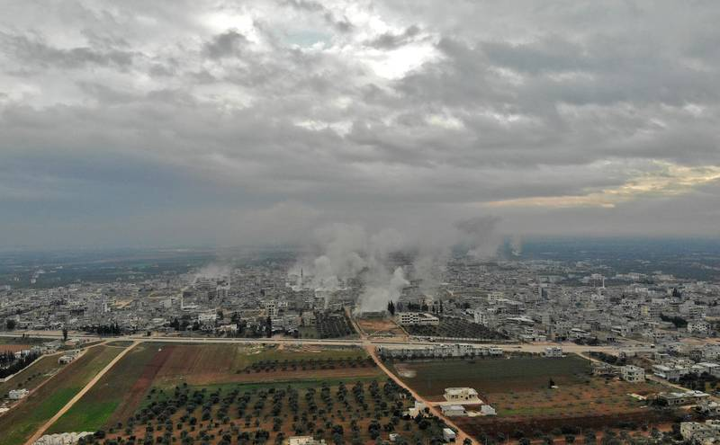 This picture taken on February 4, 2020 shows an aerial view of smoke plumes billowing from bombardment by the Syrian government forces and allies on the town of Sarmin, southeast of the city of Idlib in the northwestern province of the same name. (Photo by Omar HAJ KADOUR / AFP)