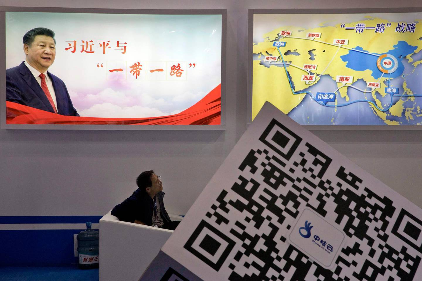 """FILE - In this April 28, 2017, file photo, an attendee at a conference looks up near a portrait of Chinese President Xi Jinping with the words """"Xi Jinping and One Belt One Road"""" and """"One Belt One Road strategy,"""" in Beijing. Seventy-five years after Japan's surrender in World War II, and 30 years after its economic bubble popped, the emergence of a 21st century Asian power is shaking up the status quo. As Japan did, China is butting heads with the established Western powers, which increasingly see its growing economic and military prowess as a threat. (AP Photo/Ng Han Guan, File)"""